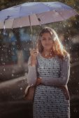Young fashion woman with umbrella.  Filtered image with blurry rain — Stock Photo