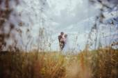 Beautiful bride and groom standing in grass and kissing. Wedding couple fashion shoot. — Stock Photo