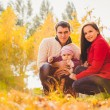 Picture of lovely family in autumn park, young parents with nice adorable kids playing outdoors, five cheerful person have fun on backyard in fall, happy family enjoy autumnal nature — Stock Photo #57516921