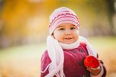 Little girl eating apple in autumn — Stock Photo