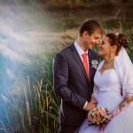 Beautiful lovely bridal couple standing near lake — Stock Photo #59535745