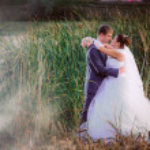 Beautiful lovely bridal couple standing near lake — Stock Photo #59535765