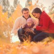 Happy young family spending time outdoor in the autumn park — Stock Photo #59629731