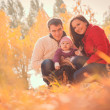 Happy young family spending time outdoor in the autumn park — Stock Photo #59629867