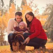 Happy young family spending time outdoor in the autumn park — Stock Photo #59629959