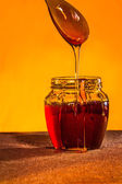 Honey jar with spoon and flowing honey,  canvas background — Stock Photo