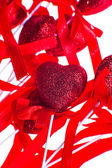 Red valentine heart shaped decorations with ribbon and bows isolated over white background. — Stock Photo
