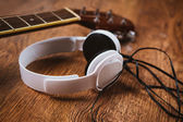 Acoustic guitar and headphone on fabric sofa — Stock Photo