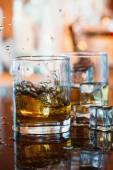 反射、温かみのある雰囲気の黒いテーブルの上の氷と暖かい光とウィスキー グラス — ストック写真