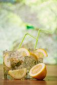 Lemonade with fresh lemon and mint by lemon reamer — Stock Photo