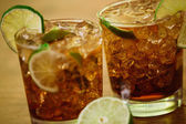 Drink concept - cocktail with cola ice cubes and lime — Stock Photo