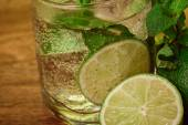 Mojito cocktail with fresh lime on wood table — Stock Photo