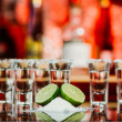 Two shots of tequila with lime and salt on a wooden table bar on the background of bright lights of the bar — Stock Photo #70274279