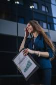 Successful beautiful young business woman standing against a background of buildings and holding folder. — Stok fotoğraf