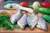 Fish and components for her preparation: vegetables, spices, par — Stock Photo