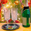 Christmas holiday, wine and glasses near a Christmas fir-tree. — Stock Photo #53716749