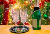 Christmas holiday, wine and glasses near a Christmas fir-tree. — Stock Photo