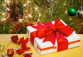 Beautifully packed gift by Christmas and the decorated fir-tree. — Stock Photo