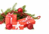 Three gift boxes with ribbon bows, Christmas tree branch and red balls on white — Stock fotografie