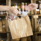 Giving a brown paper bag on a shop with the hands — Foto de Stock