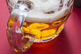 Golden frothy beer on a glass jar — Stock Photo
