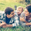 Happy family of three lying in the grass in autumn — Stock Photo #56843581