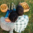 Couple resting on the grass in autumn after picking apples — Stock Photo #56844569