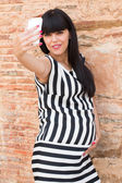 Beautiful pregnant woman making a selfie with mobile — Foto de Stock