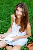 Girl writting in a notebook sitting in the grass — Photo
