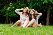 Girl friends posing with hats — Stock Photo