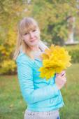 Blonde girl with yellow maple leaf — Stock Photo