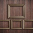 Four photo frames on wooden wall — Stock Photo #63350827