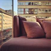 Purple sofa in a room with city view — Foto Stock
