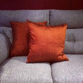 Orange cushions on gray sofa — Stock Photo