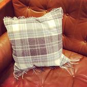 Leather sofa with checked cushion — Stok fotoğraf
