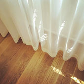 White curtain in a room with wooden floor — Photo