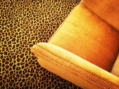 Orange velvet armchair on leopard carpet — Zdjęcie stockowe