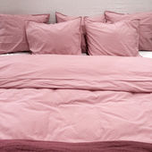 Bed with pink bedclothes — Stock Photo