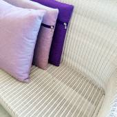 Purple cushions decorating rattan sofa — Stok fotoğraf
