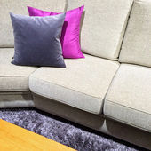 Sofa with purple cushions on a fluffy carpet — Foto de Stock