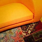 Ljusa orange soffa på färgglada mattan — Stockfoto