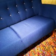 Blue textile sofa on a colorful carpet — Stock Photo #62812183