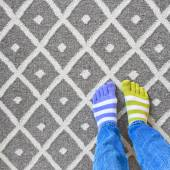 Legs in mismatched socks on gray carpet — Stock Photo