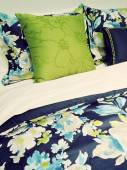Blue and green bed linen with floral design — Stock Photo
