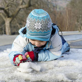 Child plying with snow and ice — Stock Photo