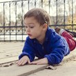 Child laying on ground outside — Stock Photo #54227777