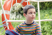 Child on a boat with safety ring l — Stock Photo