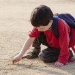 Child drawing into sand — Stock Photo #64784759