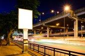 Blank advertising panel near road at night. — Stock Photo