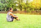 Biegacz kobieta siedzi z wody mineralnej po uruchomieniu. — Zdjęcie stockowe